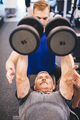 Senior man lifting weights assisted by gym instructor - PhotoDune Item for Sale