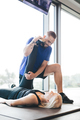 Personal trainer stretching woman's leg. - PhotoDune Item for Sale