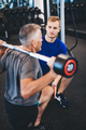Personal trainer and senior man exercising at the gym. - PhotoDune Item for Sale