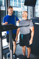 Personal trainer giving instructions to older man at the gym - PhotoDune Item for Sale