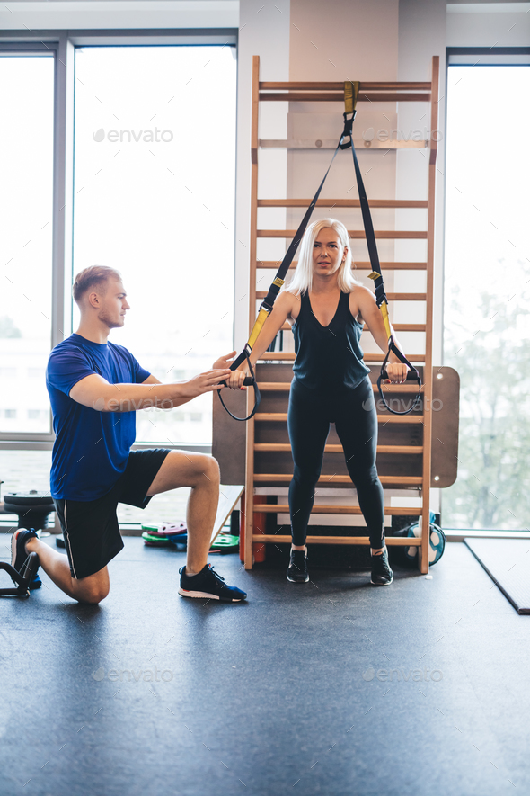 Young man assisting an exercising woman. - Stock Photo - Images