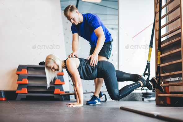 Woman exercising with personal trainer at the gym. - Stock Photo - Images