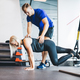 Woman exercising with personal trainer at the gym. - PhotoDune Item for Sale