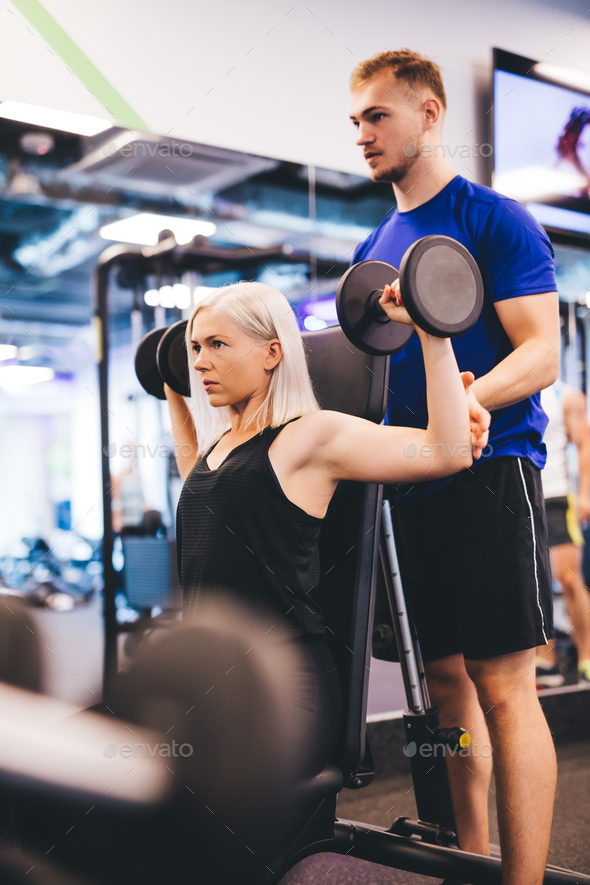 Woman at the gym exercising with personal trainer. - Stock Photo - Images
