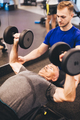 Personal trainer assisting older man in an exercise - PhotoDune Item for Sale