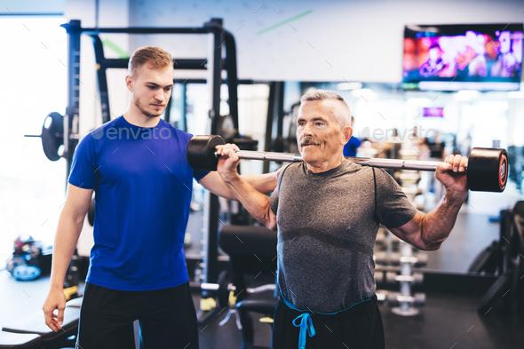 Older man assisting senior man at the gym. - Stock Photo - Images
