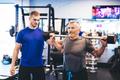 Older man assisting senior man at the gym. - PhotoDune Item for Sale