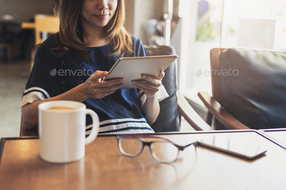 Young woman using smart phone in coffee shop drinking coffee - Stock Photo - Images