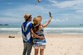 Loving couple traveler making selfie on the tropical beach - PhotoDune Item for Sale