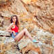 Beautiful young woman sitting on the rock, in the afternoon, in - PhotoDune Item for Sale