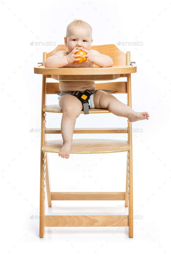 Cute baby girl eating peach and smiling while sitting in high ch - Stock Photo - Images