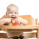 Cheerful baby girl eating apple while sitting in high chair over - PhotoDune Item for Sale