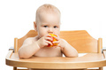 Cute baby girl eating peach while sitting in high chair over whi - PhotoDune Item for Sale