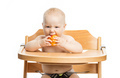 Cute baby girl eating peach while sitting in high chair - PhotoDune Item for Sale