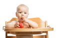 Cute baby girl eating tomato while sitting in high chair  - PhotoDune Item for Sale