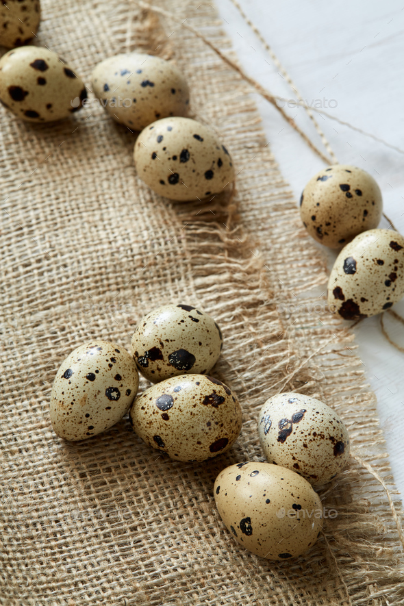 Flatview of some quail eggs on sacloth background - Stock Photo - Images
