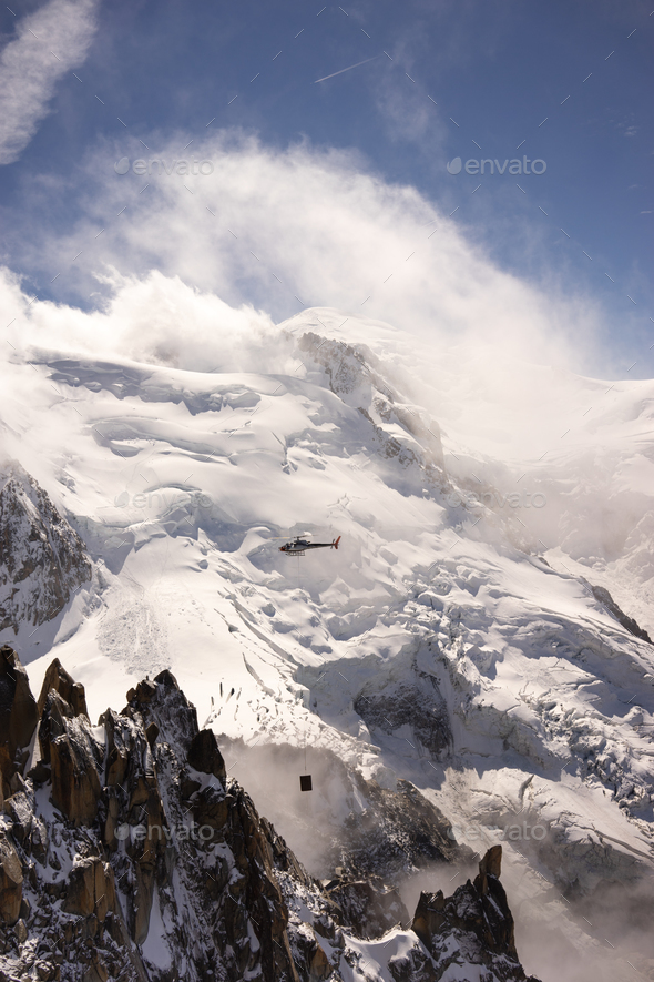 Helicopter flying in the Alps - Stock Photo - Images