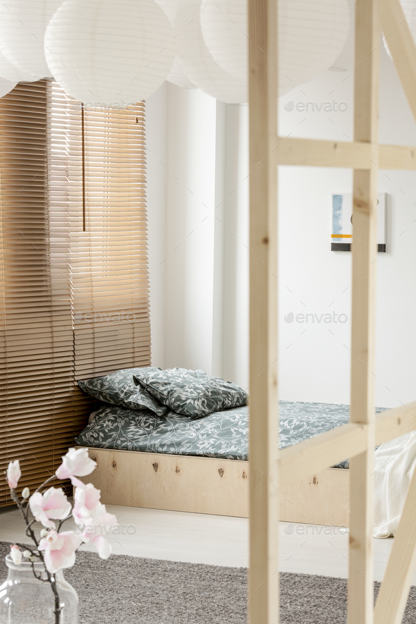 Flowers and blinds in white bedroom interior with patterned cush