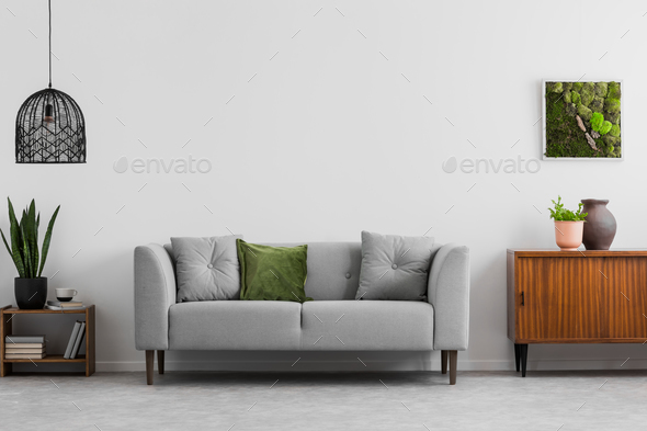 Grey sofa with pillows next to wooden cupboard in living room in