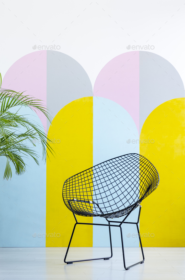 Modern armchair set on a colorful wall next to a plant. Real pho - Stock Photo - Images