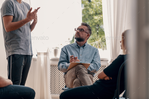 Psychotherapist listening to his patient's confession during gro - Stock Photo - Images