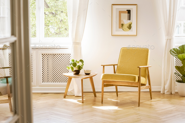 A retro, yellow armchair and a wooden table in a beautiful, sunn - Stock Photo - Images