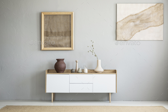 Front view of burlap artworks on a light gray wall above a woode - Stock Photo - Images