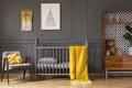 Real photo of a baby room with yellow cot standing between an ar - PhotoDune Item for Sale