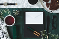 Top view of cup of tea next to white envelope on green backgroun - PhotoDune Item for Sale