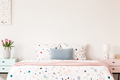 Real photo of a double bed with dotted sheets and pillows on an - PhotoDune Item for Sale