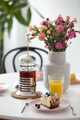Flowers and orange juice on table with tea and dessert in a rest - PhotoDune Item for Sale