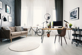 Modern home office interior with a big window, sofa, bike and de - PhotoDune Item for Sale