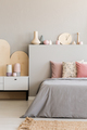 Pink pillows on grey bed with headboard in bedroom interior with - PhotoDune Item for Sale