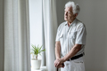 Lonely elderly man with walking stick standing by the window alo - PhotoDune Item for Sale