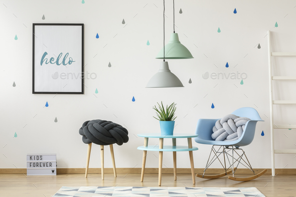 Pillow on blue rocking chair next to table with plant in child's - Stock Photo - Images