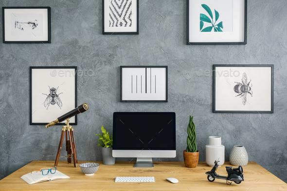 Telescope and desktop computer on wooden desk in grey workspace - Stock Photo - Images