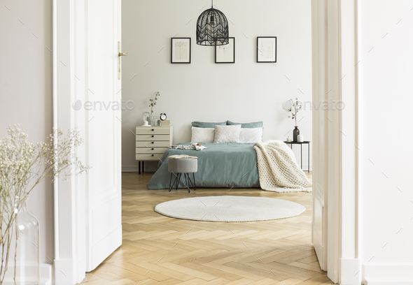 Real photo of white bedroom interior with round rug, king-size b