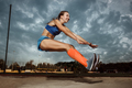 Female athlete performing a long jump during a competition - PhotoDune Item for Sale
