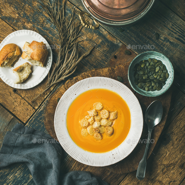Warming pumpkin cream soup with croutons and seeds on board - Stock Photo - Images