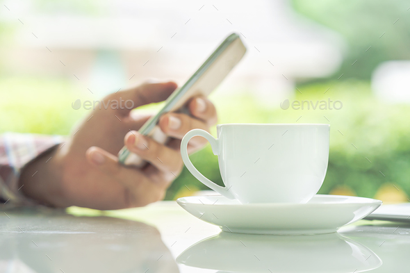 Male hands holding smart phone and cup of coffee on the table-3 - Stock Photo - Images