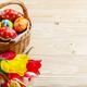 Easter eggs in wicker basket and colorful tulip flowers on woode - PhotoDune Item for Sale