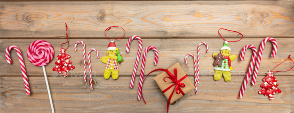 Candy Canes Christmas Ornaments And A Gift Box With Red Ribbon On Wooden Background Banner