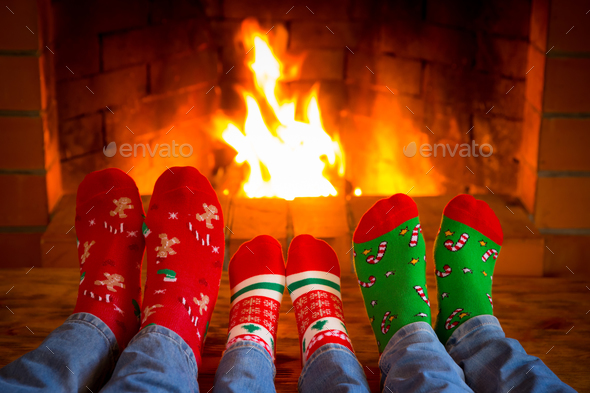 Family in Christmas socks near fireplace - Stock Photo - Images