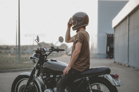 biker guy isits on classic style motorcycle - Stock Photo - Images