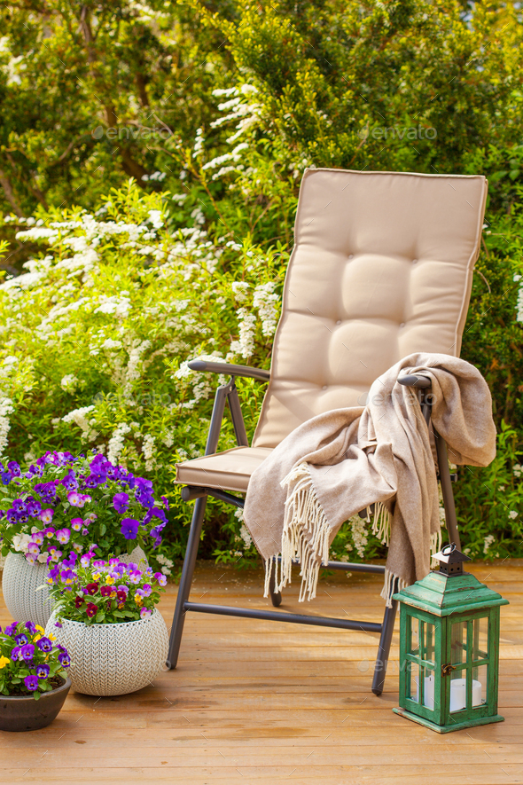 garden chair on terrace in sunlight, pansy flowers - Stock Photo - Images