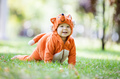 Happy baby girl dressed in fox costume crawling on lawn in park - PhotoDune Item for Sale