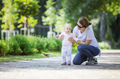 Mother supporting baby daughter and helping her make first steps - PhotoDune Item for Sale