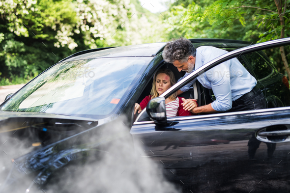 A man helping a young woman to get out of the car after a car accident. - Stock Photo - Images