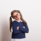 Free Download A small sad schoolgirl with glasses and uniform standing in a studio, arms crossed. Nulled
