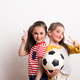 Free Download Small girls with a soccer ball standing in a studio, showing victory sign. Nulled
